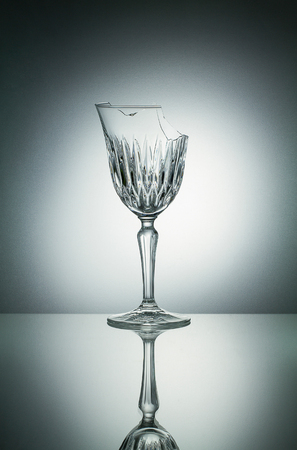 crystal glass: Broken crystal  glass with reflection on white illuminated background Stock Photo