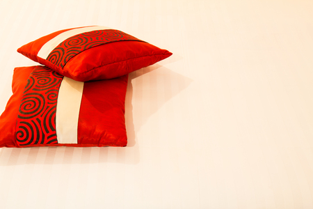 red pillows: Two lovely red pillows on the white bed in bedroom