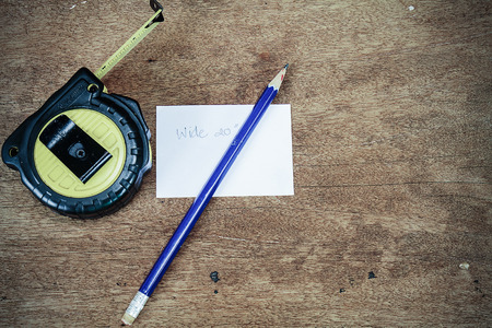 cintas metricas: Measuring tape, pencil, white paper on wooden background in vintage style