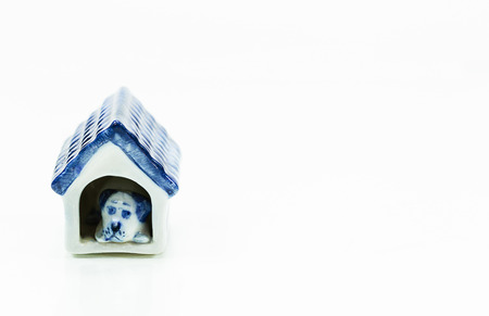 adeptness: Blue ceramic dog in a dog house figurine on white background