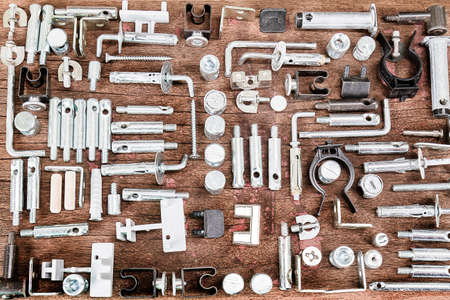 spare parts: Mixed sorted old small construction spare parts on grunge wooden background in vintage style