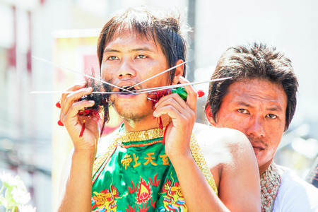 body piercing: Phuket, Thailand - Oct 14, 2015 : Unidentified participant performing body piercing,  Phuket vegetarian festival. It is annually event.