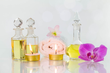 perfumed candle: Vintage old bottles of aromatic oils with burned candles, flowers  and white towel on glossy white table on white background with bokeh, aromatherapy concept