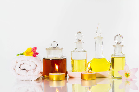 perfumed candle: Vintage old bottles of aromatic oils with candles, flowers  and white towel on glossy white table on white background, aromatherapy concept