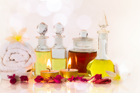 perfumed candle: Vintage old bottles of aromatic oils with burned candles, flowers  and white towel on glossy white table on white background with soft pink bokeh, aromatherapy concept