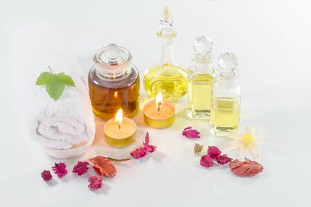 perfumed candle: Vintage old bottles of aromatic oils with burned candles, flowers, green maple leaf  and white towel on glossy white table on white background, aromatherapy concept soft tone