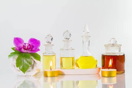 perfumed candle: Vintage old bottles of aromatic oils with candles, flowers, green leaf  and white towel on glossy white table on white background, aromatherapy concept