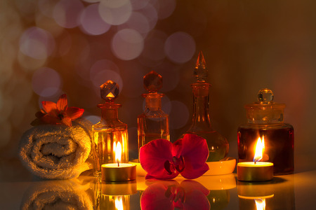 perfumed candle: Still life, vintage old bottles of aromatic oils with burned candles, pink orchid  and white towel on glossy table on blurred pink bokeh background, aromatherapy concept Stock Photo