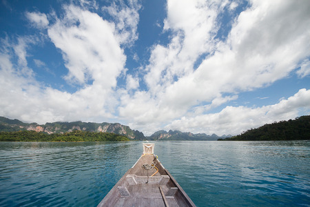 Head of wooden boat cruising in the lake with mountains view and cloudy blue sky background in Surat thani, Thailand Stock Photo