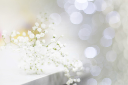 Blurred white gypsophila flowers on white table on blurred bokeh