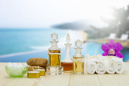 perfumed candle: Bottles of aromatic oils with candles, pink orchid, stones and white towel on vintage wooden floor on blurred pool and beach background, spa treatment concept