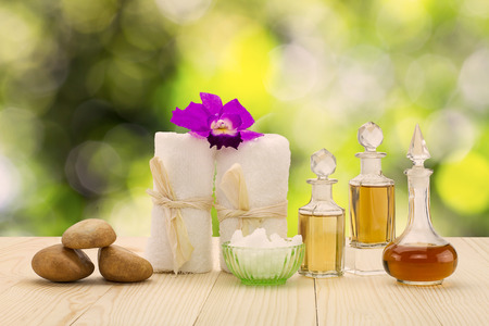 Bottles of aromatic oils with  pink orchid, stones and white towel on vintage wooden floor on blurred green bokeh background, spa treatment concept
