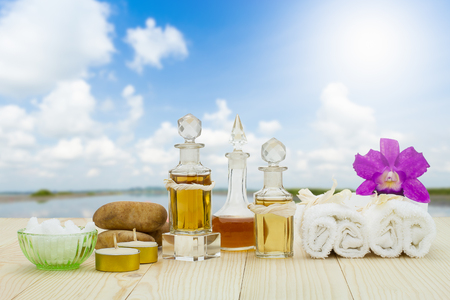 perfumed candle: Bottles of aromatic oils with candles, pink orchid, stones and white towel on vintage wooden floor on blurred lake with cloudy blue sky background, spa treatment concept Stock Photo