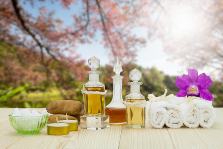 perfumed candle: Bottles of aromatic oils with candles, pink orchid, stones and white towel on vintage wooden floor on blurred lake and forest background, spa treatment concept