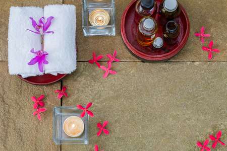 perfumed candle: Aromatic oil in grunge wooden bowl, burned candle, pink flowers, white towel on vintage grunge stone background, spa treatment concept Stock Photo