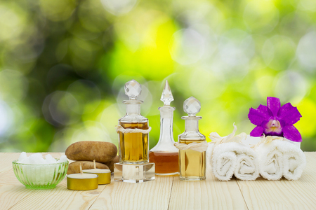 perfumed candle: Bottles of aromatic oils with candles, pink orchid, stones and white towel on vintage wooden floor on blurred green bokeh background, spa treatment concept Stock Photo