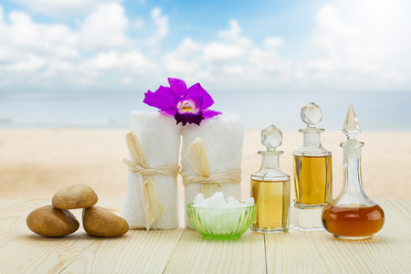 perfumed candle: Bottles of aromatic oils with  pink orchid, stones and white towel on vintage wooden floor on blurred beach with cloudy blue sky background, spa treatment concept
