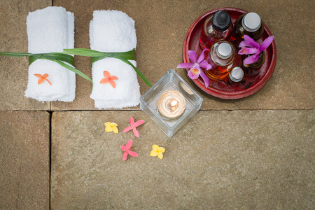 perfumed candle: Aromatic oil in grunge wooden bowl, burned candle, pink yellow orange flowers, white towel on vintage grunge stone background, spa treatment concept