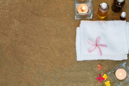 perfumed candle: Aromatic oil, burned candle, pink yellow orange flowers, white towel on vintage grunge stone background, spa treatment concept