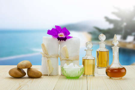 perfumed candle: Bottles of aromatic oils with  pink orchid, stones and white towel on vintage wooden floor on blurred pool and beach background, spa treatment concept