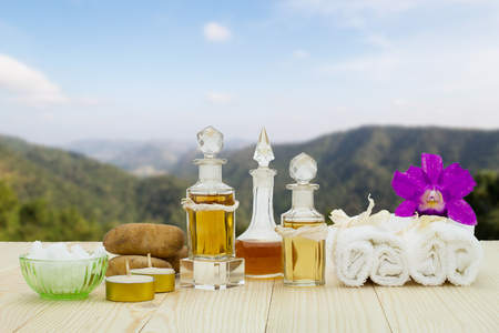 perfumed candle: Bottles of aromatic oils with candles, pink orchid, stones and white towel on vintage wooden floor on blurred mountain background, spa treatment concept