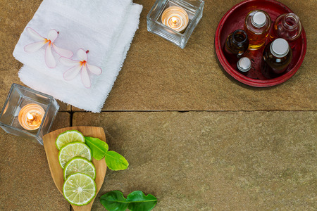 perfumed candle: Aromatic oil in grunge wooden bowl, burned candle, pink flowers, sliced  lime, green leaf, white towel on vintage grunge stone background, spa treatment concept Stock Photo