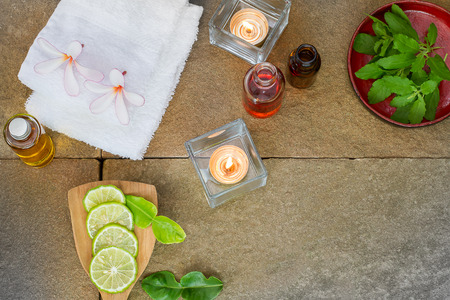 perfumed candle: Aromatic oil, burned candle, pink flowers, sliced  lime, green leaf, white towel on vintage grunge stone background, spa treatment concept Stock Photo