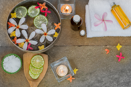 perfumed candle: Aromatic oil, burned candle, pink yellow orange flowers, sliced  lime, white towel on vintage grunge stone background, spa treatment concept Stock Photo