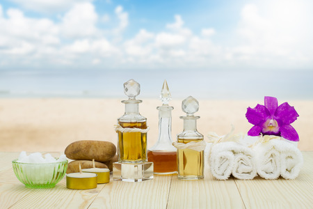 perfumed candle: Bottles of aromatic oils with  candles, pink orchid, stones and white towel on vintage wooden floor on blurred beach with cloudy blue sky background, spa treatment concept
