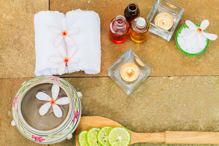 perfumed candle: Aromatic oil, burned candle, pink flowers, sliced lime, white towel on vintage grunge stone background, spa treatment concept