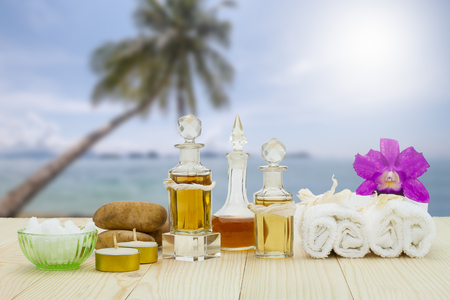 perfumed candle: Bottles of aromatic oils with candles, pink orchid, stones and white towel on vintage wooden floor on blurred beach background, spa treatment concept Stock Photo