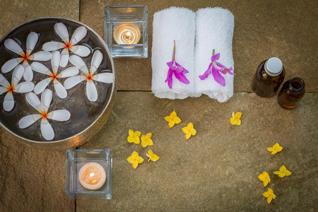 perfumed candle: Aromatic oil, burned candle, pink yellow flowers, white towel on vintage grunge stone background, spa treatment concept