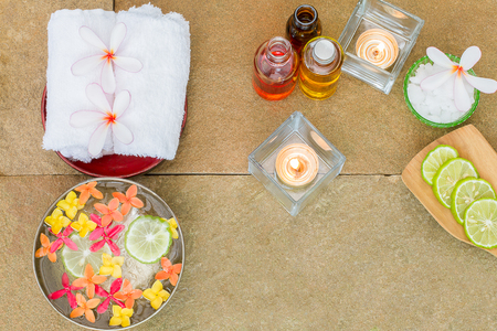 perfumed candle: Aromatic oil, burned candle, pink yellow, orange flowers, sliced lime, white towel on vintage grunge stone background, spa treatment concept