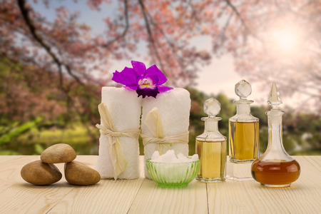 perfumed candle: Bottles of aromatic oils with  pink orchid, stones and white towel on vintage wooden floor on blurred lake and forest background, spa treatment concept Stock Photo
