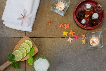perfumed candle: Aromatic oil in grunge wooden bowl, burned candle, pink yellow orange flowers, sliced  lime, green leaf, white towel on vintage grunge stone background, spa treatment concept