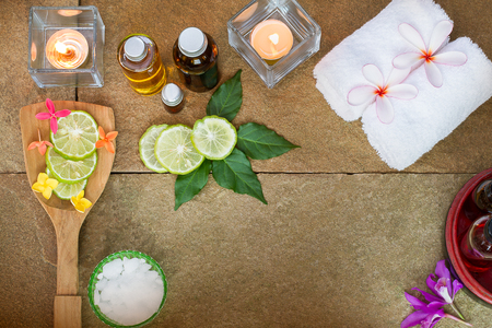 perfumed candle: Aromatic oil, burned candle, pink yellow, orange flowers, green leaves, sliced  lime,  white towel on vintage grunge stone background, spa treatment concept