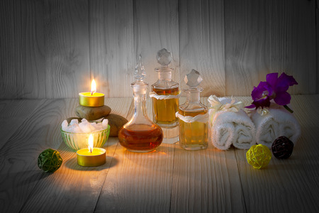 perfumed candle: Bottles of aromatic oils with candles, pink orchid, stones and white towel on vintage wooden background with vignette,spa treatment concept