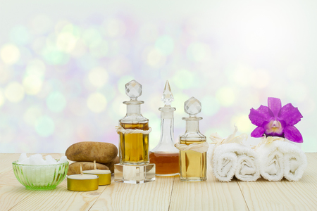 perfumed candle: Bottles of aromatic oils with candles, pink orchid, stones and white towel on vintage wooden floor on blurred  bokeh background, spa treatment concept Stock Photo