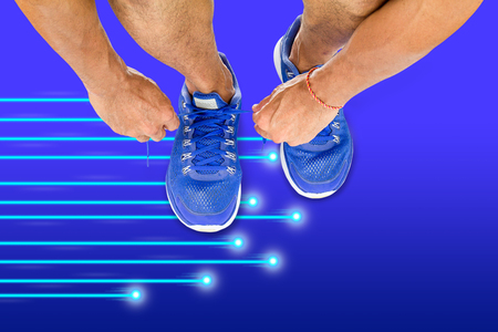 Man lacing sport shoes on the floor with blue  light moving background, science sport exercise technology concept
