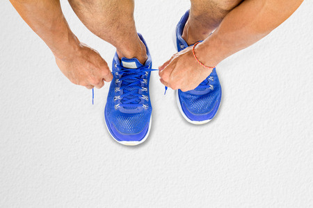 Man lacing sport shoes on white floor in fitness, sport exercise concept