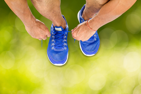 Man lacing sport shoes on blurred green bokeh background, sport exercise concept