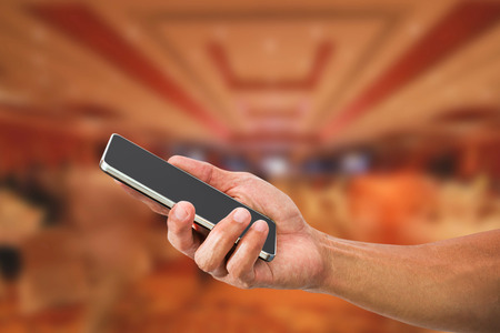 man's: Mans hand holding mobile phone on blurred hotel lobby