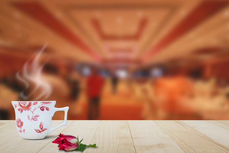 Hot coffee with steam and red flower on wooden table top on blurred hotel lobby background
