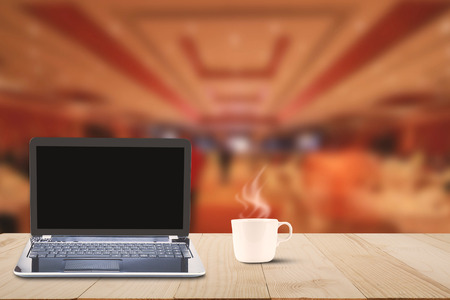 Computer laptop with black screen and hot coffee cup on wooden table top on blurred hotel lobby background, business concept Stock Photo