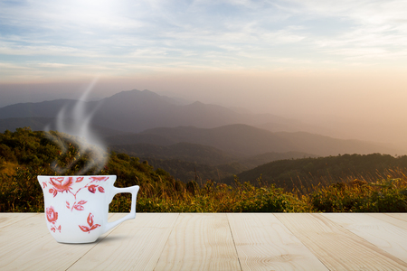 resort life: Hot coffee cup with steam on vintage wooden table top on blurred meadow and foggy mountain background during sunrise