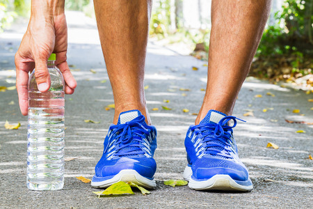 Man wearing sport shoes and picking up water bottle on running track in park, sport exercise concept