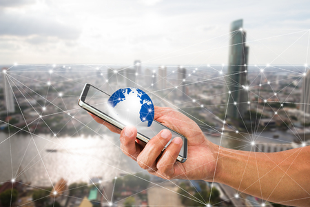 man's: Mans hand holding mobile phone with globe on blurred city background, technology communication connection concept
