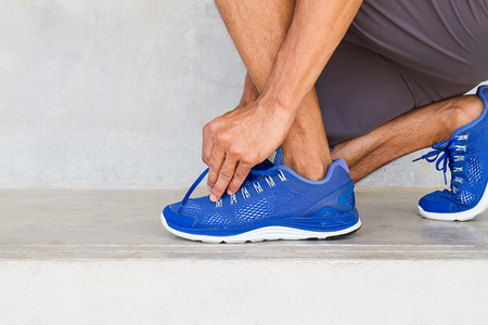 shoelace: Man lacing sport shoes in gym, sport exercise concept
