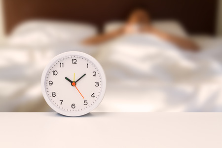 White alarm clock on white desk on blurred man sleeping on white bedding sheet, time concept