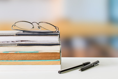 Eyeglasses on books and pens on white table on blurred library background